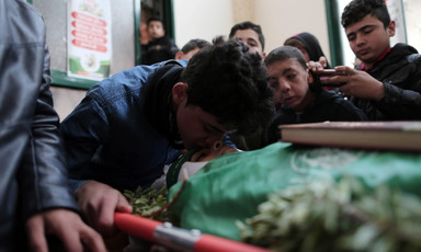 Boy kisses forehead of shrouded body on stretcher