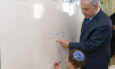 Man in suit looks over a child as he writes on whiteboard