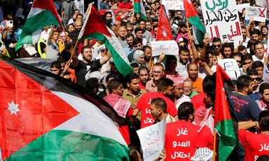Crowd of dozens carry Jordanian flags, banners