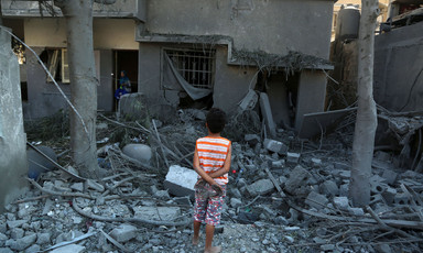 Back view of child looking at rubble of bombed-out building