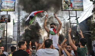 Man holding Palestinian flag carried by other men with backdrop of smoke