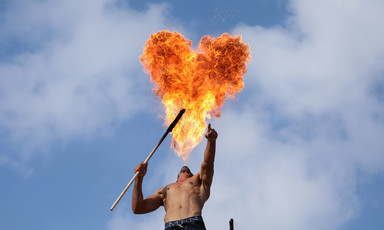 Heart-shaped cloud of fire hangs over a shirtless man