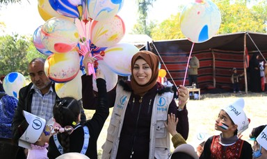 A charity worker hands out ballons to children