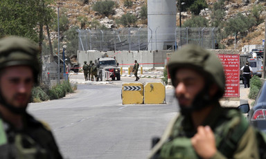 Soldiers stand n front of military tower and roadblocks