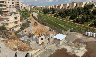 Landscape view of Palestinian community next to Israeli wall and settlement