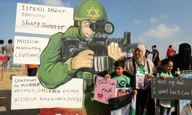 Woman and children stand in front of giant cut-out of soldier holding rifle