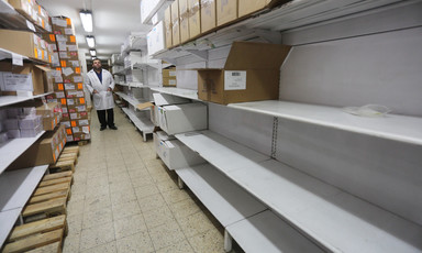 Man stands behind shelves, many of them empty.
