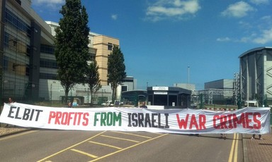 Seven activists hold up a huge banner against Israeli war crimes