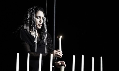 Woman lighting menorah candles