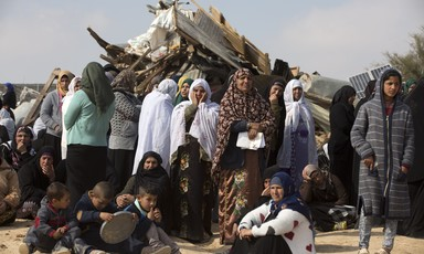Women and children stand and sit in front of rubble of destroyed structure