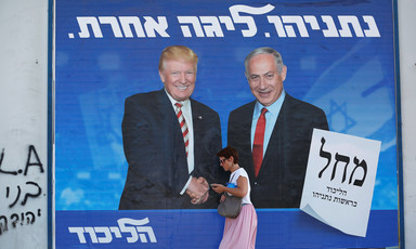 Woman walks past billboard of Trump and Netanyahu
