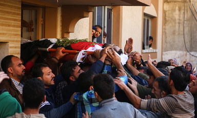 Body sheathed in flag is carried out of home by crowd of men