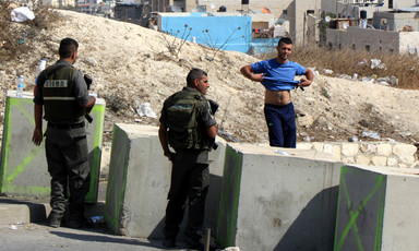 Two soldiers behind concrete blocks look at a young man who has lifted his t-shirt to show his stomach