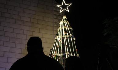Silhouette of a man near a lit Christmas tree