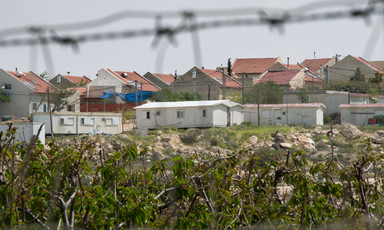 Landscape view of settlement homes with barbed wire in foreground