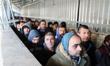 Men queue in a concrete walkway
