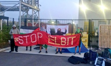 Masked protesters with a large banner block a factory gate