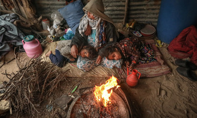 A woman and two children sitting near fire