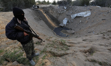 Masked man holding gun stands near sandy crater