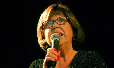 A woman holds a microphone