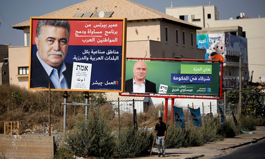 Two men are seen on two separate election posters in front of a house