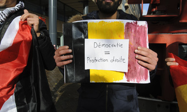 Man holds black, yellow and red placard