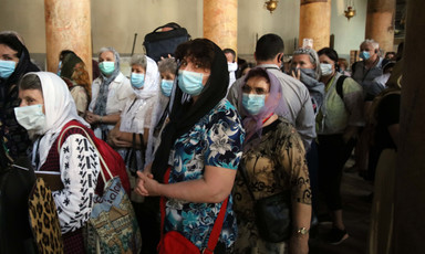 People wear paper masks over their mouths while standing next to pillars
