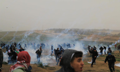 People in a field run amid streaks of smoke