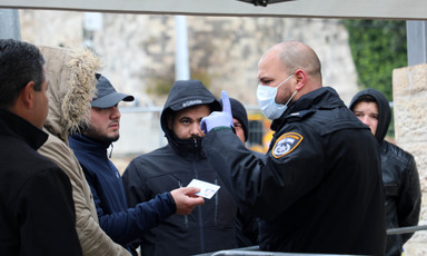 Uniformed man in protective face mask raises finger at group of men without masks