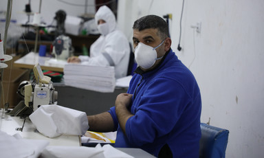 People wearing protective gear work at sewing machines