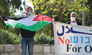 Two men wearing face masks hold Palestine flag and banner