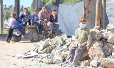 Boy wearing face mask sits on rubble with family in background