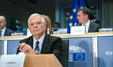 Man sits at podium touching microphone