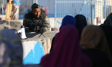 Soldier pointing rifle leans over women at checkpoint