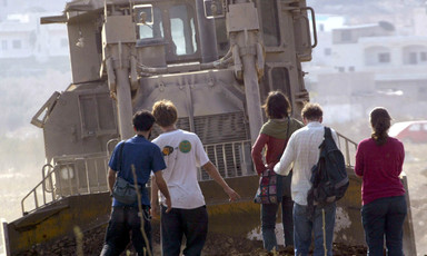 A group of people appears small next to an armored bulldozer