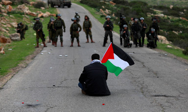 A man holding a Palestine flag sits on a road facing a line of soldiers