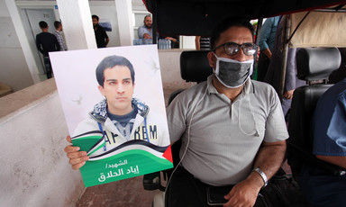 Man in wheelchair holds poster of Iyad Hallaq