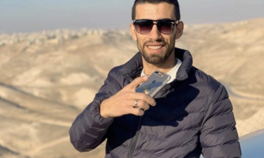 Man smiles and holds phone against backdrop of mountains