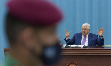 Mahmoud Abbas gestures behind the blurred profile of a Palestinian security officer