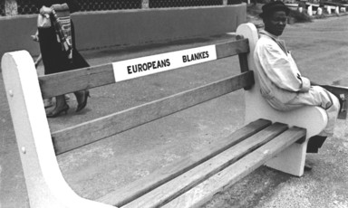 Man sits on edge of bench that says Europeans Only