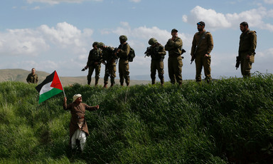 A man waves a Palestinian flag in front of a group of Israeli soldiers