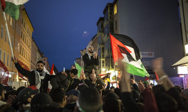 Evening protest where people wave Palestinian flags