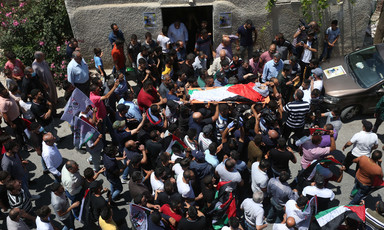 Crowd carries body on stretcher wrapped in Palestine flag