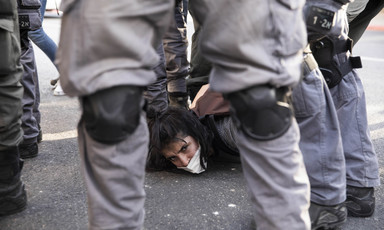 Israeli police stand around woman on ground looking toward camera
