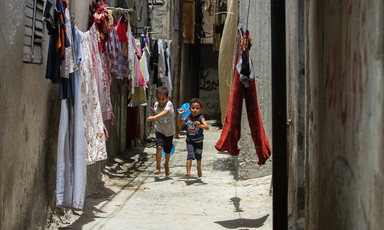 Two children play in a narrow alley where washing has been hung