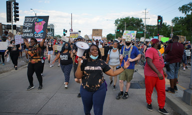 Woman with megaphone leads marching protesters
