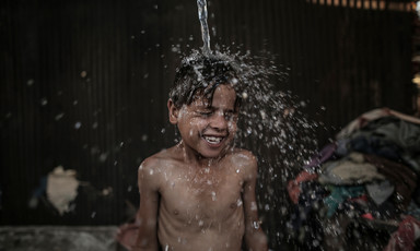 A boy smiles as water is poured over his head