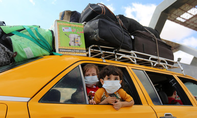 Two children wearing masks look out a car window
