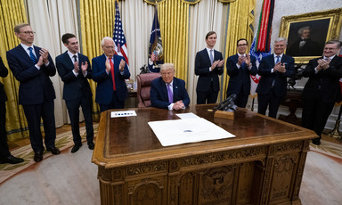 Man sits behind desk surrounded by men