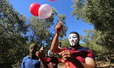 Man with mask holds a number of balloons